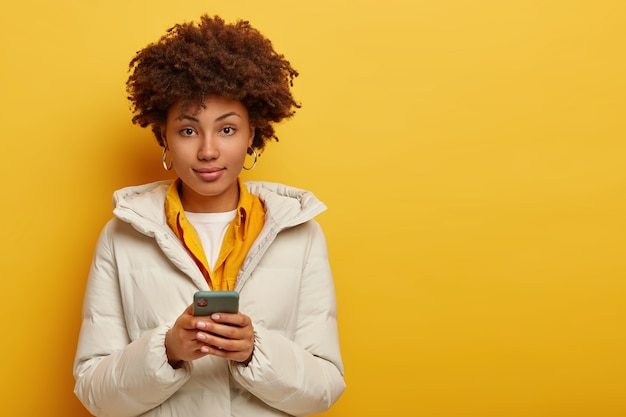 Stylish attractive woman in white warm coat, looks directly at camera, uses modern cell phone for chatting online, has curly haircut, isolated over yellow background. people and modern technology