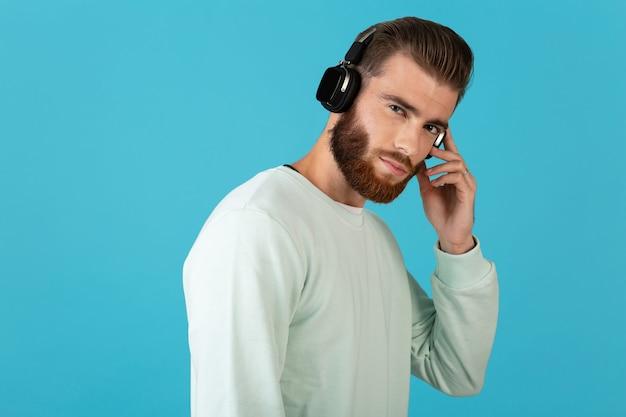 Стильный привлекательный молодой бородатый мужчина слушает музыку на беспроводных наушниках в современном стиле уверенное настроение, изолированное на синей стене
