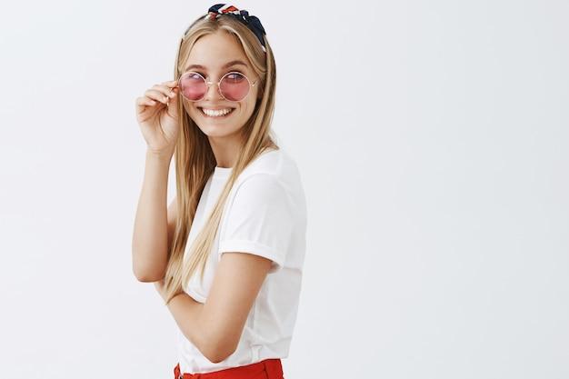 白い壁にポーズをとってスタイリッシュな魅力的な若いブロンドの女の子