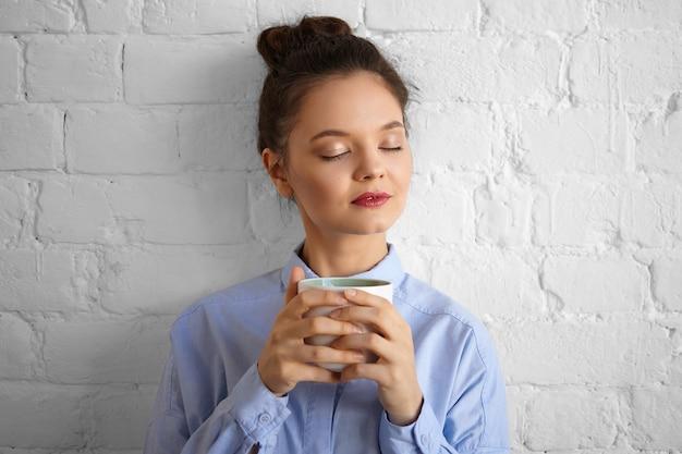 フォーマルな青いシャツを着て、ホットコーヒーを飲みながら目を閉じて、新鮮な香りを楽しんで、幸せそうに笑ってメイクアップスタイリッシュな魅力的な若いブルネットの女性サラリーマン