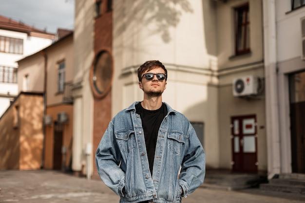 검은 선글라스에 트렌디 한 블루 데님 재킷을 입은 세련된 매력적인 젊은 힙 스터 남자는 화창한 봄 날에 도시 거리를 따라 산책을 즐깁니다. 잘 생긴 남자 모델은 건물 근처를 산책합니다.
