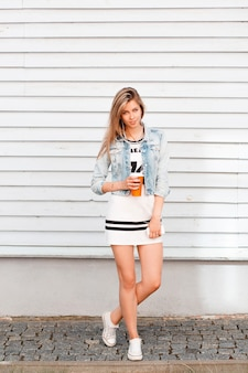 도시에있는 흰색 목조 건물 근처 포즈 흰색 운동화에 여름 데님 재킷에 스포티 한 흰색 세련 된 드레스에 세련 된 매력적인 젊은 여자. 달콤한 음료를 마시는 귀여운 소녀.
