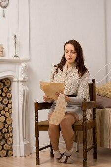 복고풍 나무 안락의 자에 긴 문서를 읽고 앉아 세련 된 매력적인 젊은 여자