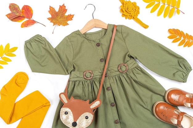 Stylish autumn set of child clothes. green dress, brown bag, shoes and yellow tights, accessories for hair and autumn leaves