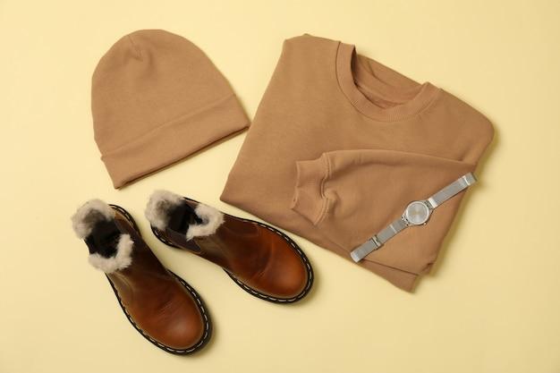 Стильная осенняя одежда на бежевой поверхности