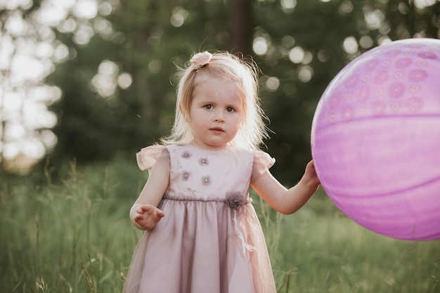 Stylish baby girl 2-5 year old holding big balloon wearing trendy pink dress in meadow. playful. little girl with a balloon in the park