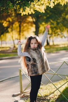 Stylish baby girl 4-5 year old wearing boots, fur coat standing in park. looking at camera. autumn fall season.