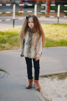Stylish baby girl 4-5 year old wearing boots, fur coat standing in park. looking at camera. autumn fall season