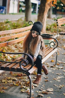 Stylish baby girl 4-5 year old wearing knitted hat, sunglasses, boots, fur coat sitting on the bench in park. looking at camera. autumn fall season.