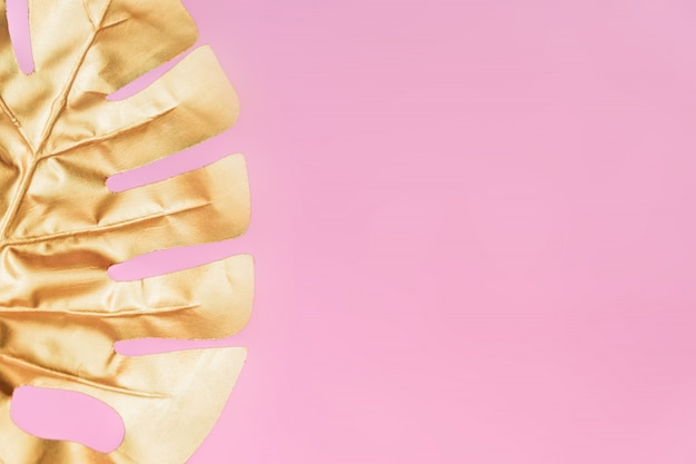Stylish background with gold leaf of monstera on pink color