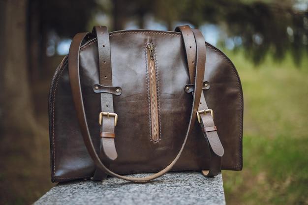 Стильный рюкзак и солнцезащитные очки на зеленой траве.