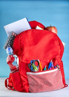 Stylish backpack with various school stationary on a white wooden table