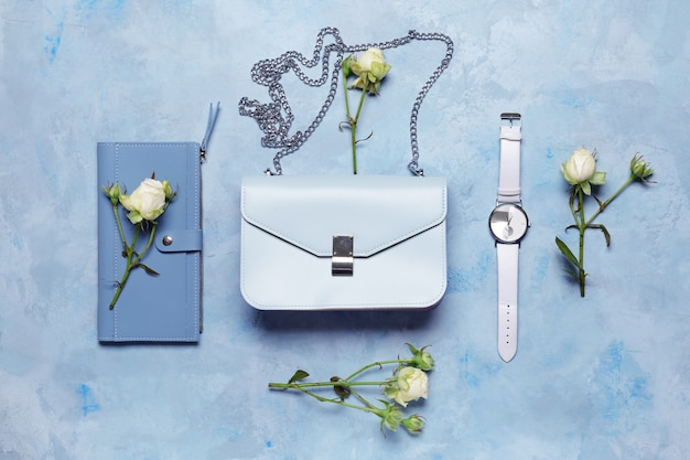 Stylish bag with wrist clock and wallet on blue