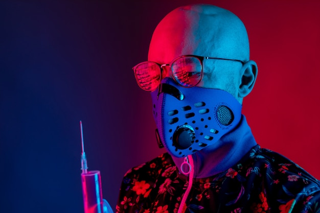 호흡기 마스크와 안경을 착용하고 백신 주사기를 들고 세련된 대머리 남자