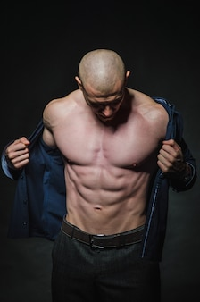 A stylish, bald young man stands with a naked torso on dark in the category.