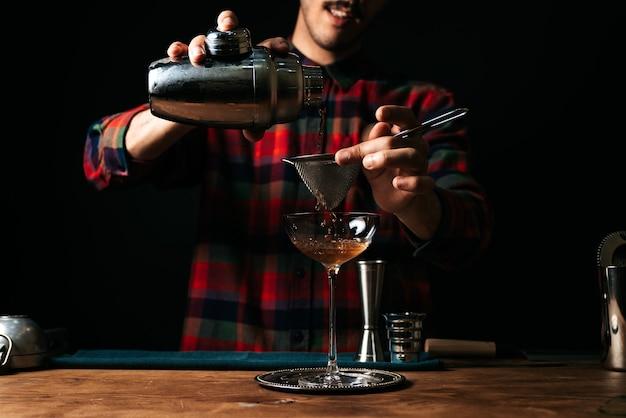 Стильный бармен наливает коктейль