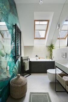 壁に緑色に塗られたパネルを備えたスタイリッシュなバスルームデザイン。浴槽、タオル、籐のバスケット、その他の身の回り品。グラマーインテリアコンセプト。レンプレート。