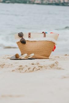 サマーバッグ、サンダル、サングラスを備えた砂浜のスタイリッシュなビーチアクセサリー。