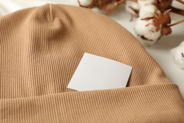 Стильная шапка и хлопок на белой поверхности