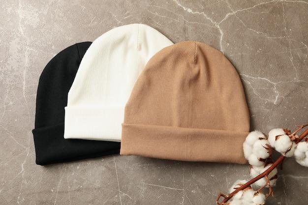Стильные шапочки и хлопок на сером фоне
