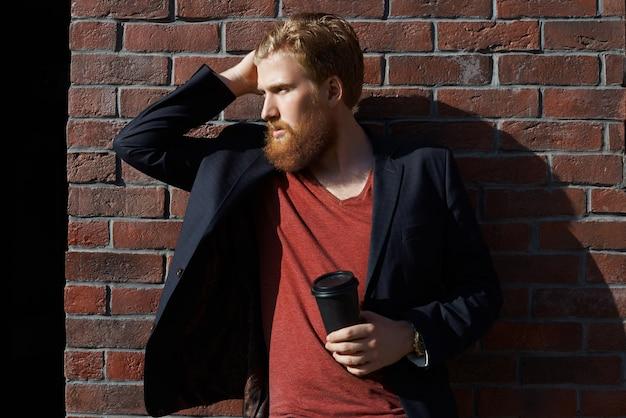スタイリッシュなひげの男がコーヒーを飲む