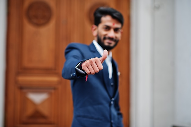Stylish beard man with bindi on forehead, wear on blue suit posed outdoor against door of building and show thumb up.