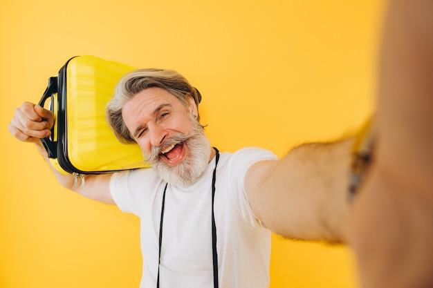 スタイリッシュなひげを生やした、口ひげを生やした男が笑みを浮かべて、黄色のスーツケースを持ってスマートフォンで自分撮りをします。