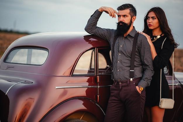 シャツとサスペンダーのズボンを着たスタイリッシュなひげを生やしたブルネットの男は、フィールドの背景にある茶色のレトロな車の近くにある黒い短いドレスを着た長い髪の細い若い女の子を抱きしめます