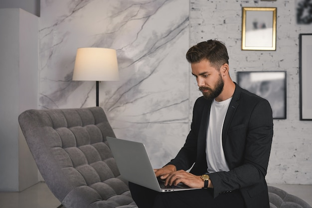 Stylish bearded businessman sitting on comfortable couch with portable computer on his laptop, typing business letter via email, having focused serious look. technology, communication and business