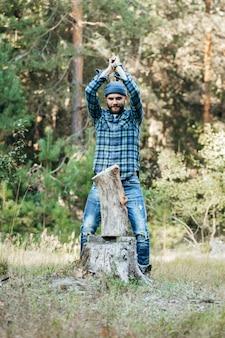 Стильный бородатый лесник рубит дрова топором