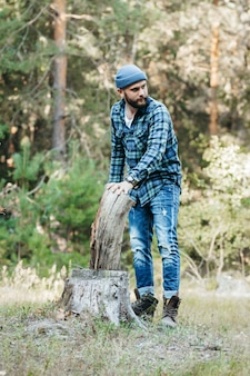 Stylish bearded forester chopping wood with an axe