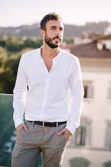 Стильный бородатый парень в белой рубашке и легких брюках на террасе на крыше во флоренции, италия