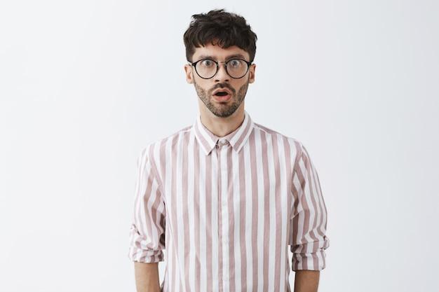 Стильный бородатый парень позирует у белой стены в очках