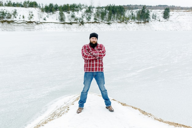 Stylish bearded guy in the winter on the lake