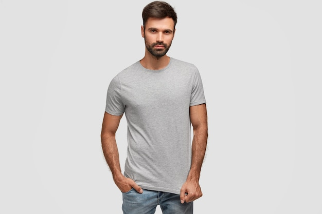 Stylish bearded handsome man with thick dark stubble, dressed in casual t shirt, keeps hand in pocket of jeans