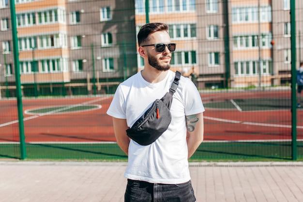 Стильный бородатый хипстер в городе в белой футболке с поясной сумкой