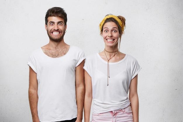 Elegante uomo barbuto in maglietta e donna carina con fascia gialla che sorride in modo innaturale mostrando i denti bianchi perfetti
