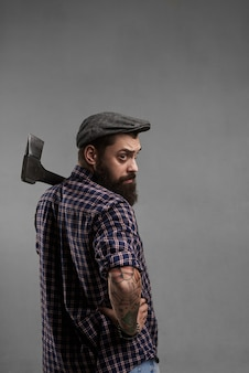 Stylish bearded man in cap and shirt with axe on shoulder look back to the camera. handsome forester shot in studio. brutal male with tattoo.