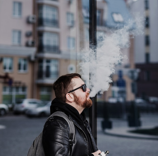 Стильный бородатый мужчина в кожаной куртке выпускает дым изо рта