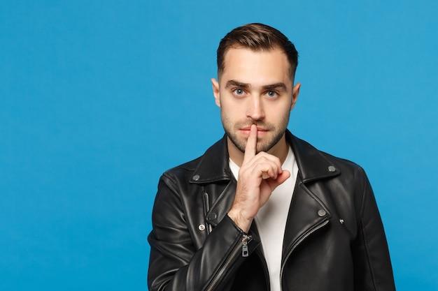 검은 가죽 재킷 흰색 티셔츠를 입은 세련된 수염 남자는 파란색 벽 배경 스튜디오 초상화에 격리된 입술에 손가락을 대고 조용히 쉿 소리를 냅니다. 사람들이 진실한 감정 개념입니다. 조롱.