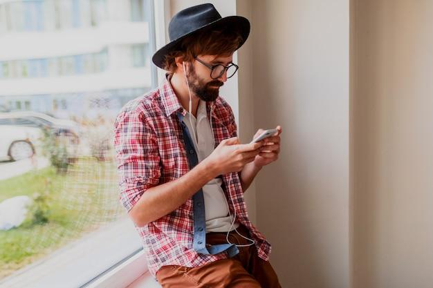Стильный бородатый мужчина в яркой клетчатой рубашке установки нового мобильного приложения на смартфон устройства и прослушивания музыки. хипстерский стиль