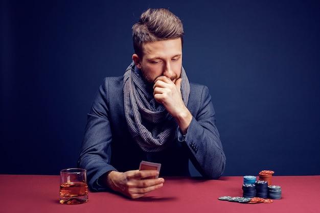어두운 카지노 흡연 시가 음료 위스키에서 재생하는 양복과 스카프에 세련된 수염 난 남자