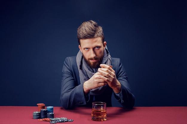 暗いカジノで遊ぶスーツとスカーフのスタイリッシュなひげを生やした男