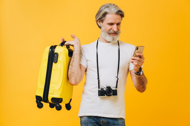 세련 된 수염 된 남자 웃 고, 노란 가방을 들고 여행 국가 선택 전화보고.