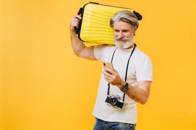 スタイリッシュなひげを生やした男が笑って、黄色のスーツケースを持って、旅行する国を選択する電話を見てください。