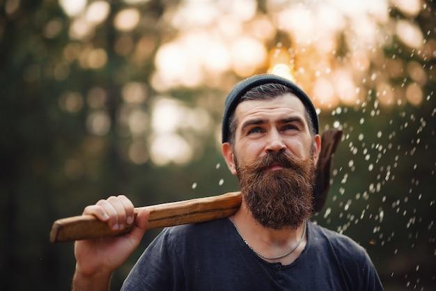 Tシャツに長いあごひげと口ひげを生やしたスタイリッシュなあごひげを生やした木こりと肩に斧をかぶった暖かい帽子