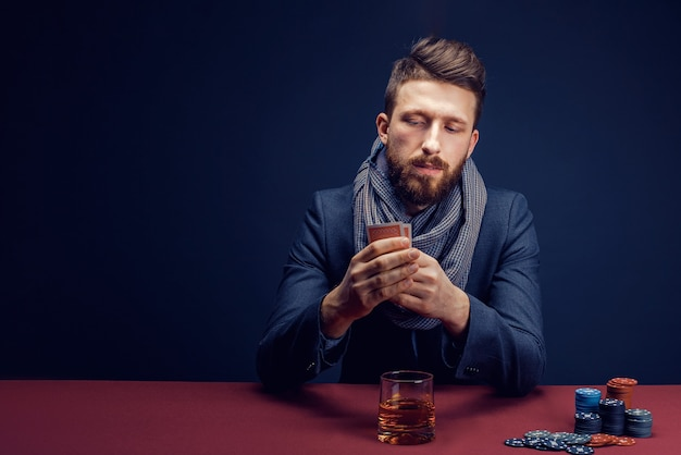 Stylish bearded man playing in dark casino drinking whiskey