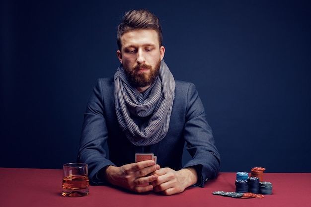 Stylish bearded man playing in dark casino and drinking whiskey