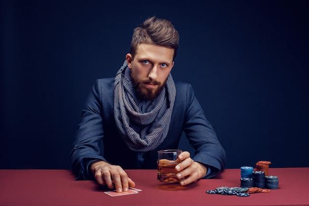Стильный бородатый мужчина играет в темном казино и пьет виски