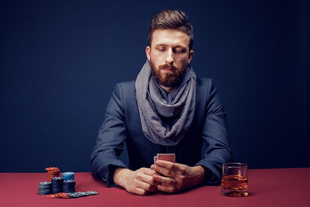 Stylish bearded man in suit and scarf playing in dark casino